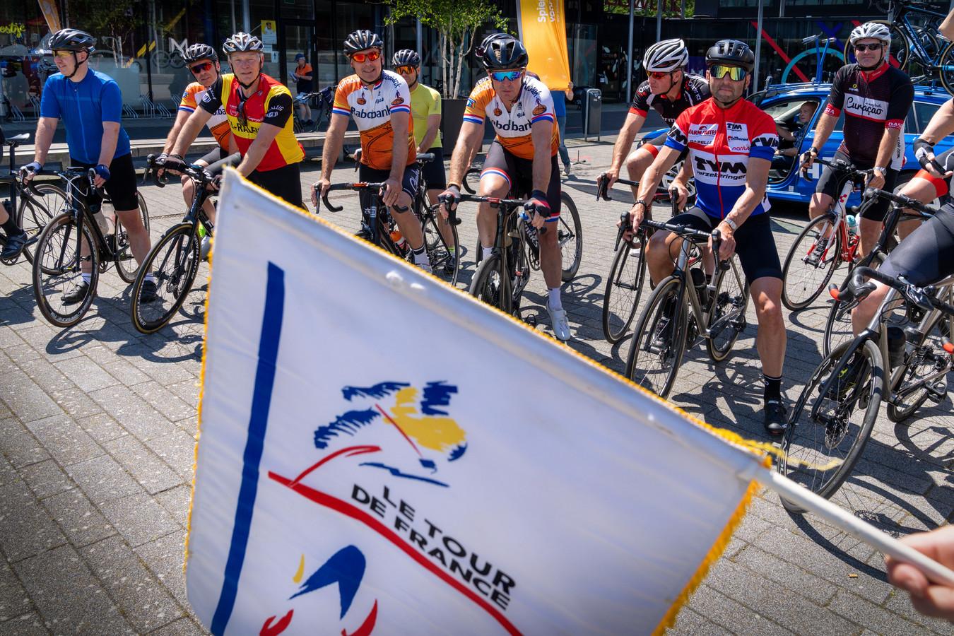 Organisator René Koppert (rood-geel shirt) wacht naast Erik Breukink, Erik Dekker, Maarten den Bakker en (de niet zichtbare Bart Voskamp) het moment af dat Minke Booij met de startvlag van toen de verkenning van de Ronde van Frankrijk in Brabant in gang schiet.