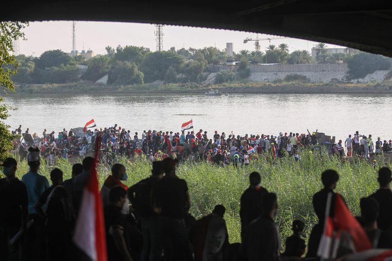 Onder de al-Jumhuriyabrug in Baghdad demonstreren duizenden Irakezen tegen de overheid. Beeld AFP