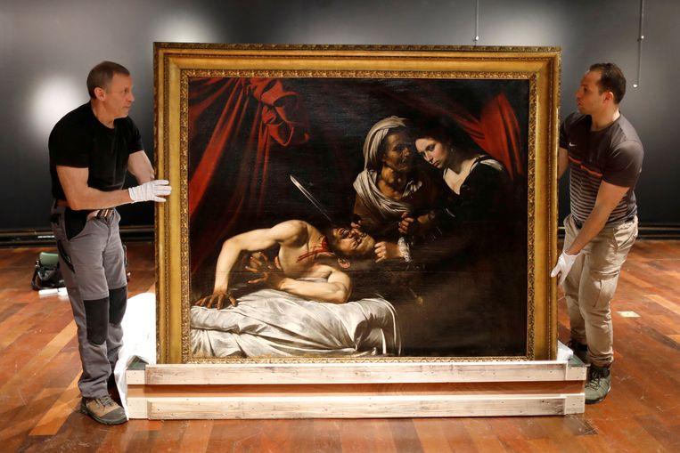 Het schilderij Judith Beheading Holofernes van Caravaggio (1571-1610) wordt opgehangen in een veilinghuis in Parijs.  Beeld REUTERS
