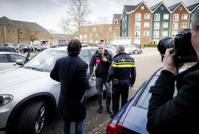 Een verslaggever van omroep Powned in gesprek met een automobilist en agent op de parkeerplaats van de Sionkerk. Beeld ANP