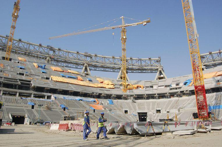 Arbeiders werken aan het Lusail-stadion in Qatar, waar de openingsmatchen de finale gespeeld zullen worden. Beeld BELGAIMAGE