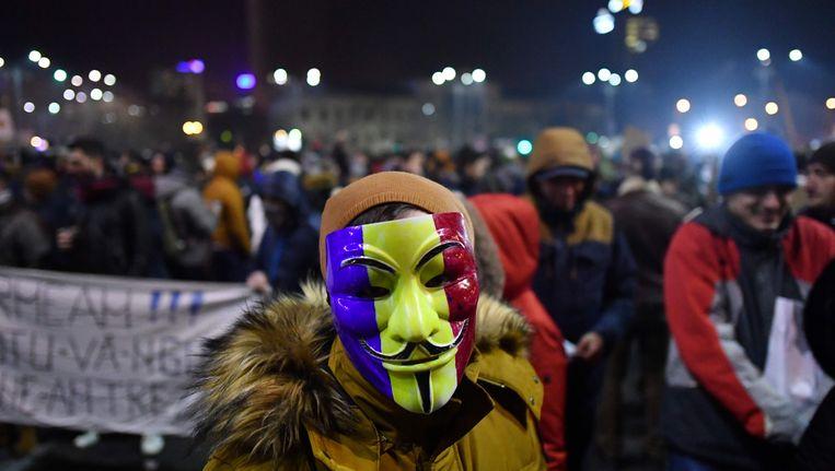 Een demonstrant donderdagavond in Boekarest. Beeld AFP