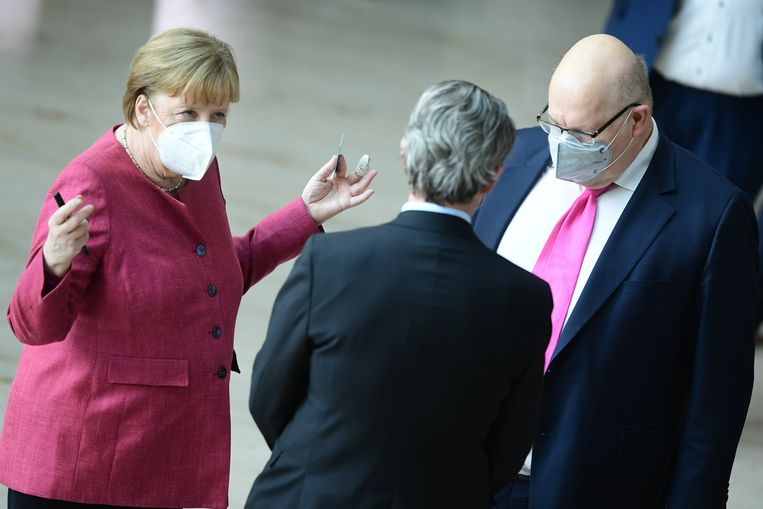 Bondskanselier Angela Merkel overlegt in de Bondsdag met haar stemkaart in de hand met de ministers van Transport en van Economische Zaken.  Beeld EPA