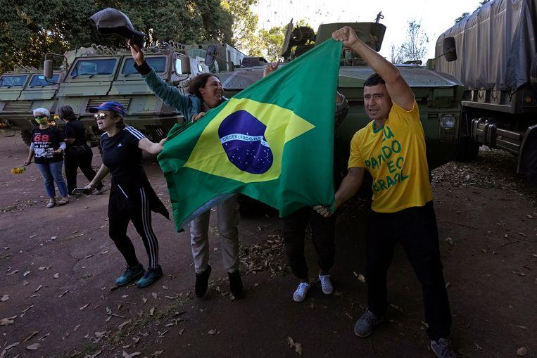 Supporters van president Bolsonaro protesteren met de Braziliaanse vlag terwijl tegenstanders van de president op de achtergrond met bloemen staan bij militaire voertuigen. Beeld  Eraldo Peres / AP