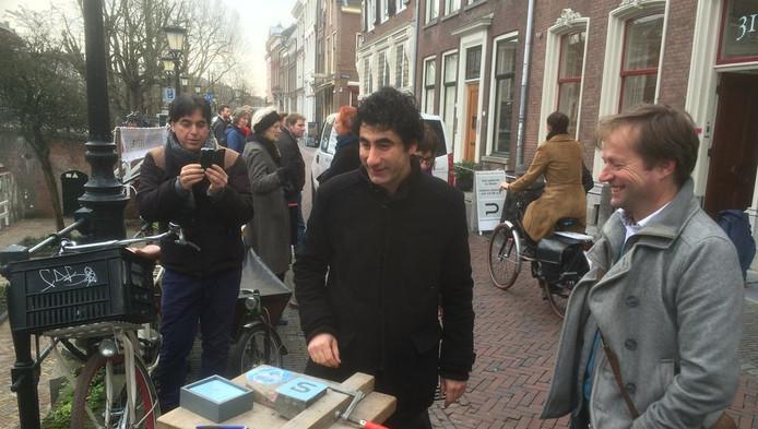 Baban Kirkuki bij de steen die zaterdagmiddag in de straat werd gelegd om het gedicht aan te vullen. Rechts dichter Ruben van Gogh, die de eerst 124 letters dichtte.