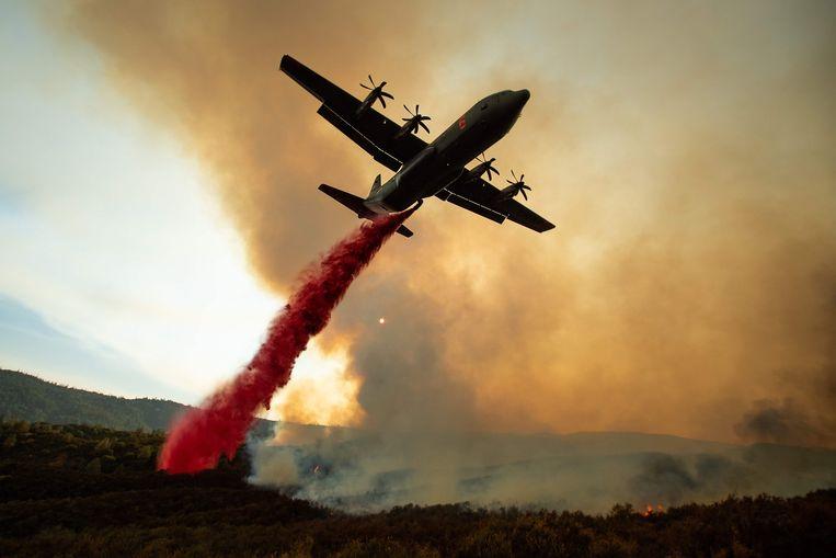 Het gebruik van blusvliegtuigen die vlamvertragers in de vorm van rood poeder afwerpen, zoals hier in Californië, zou niet altijd effectief zijn. Beeld AFP