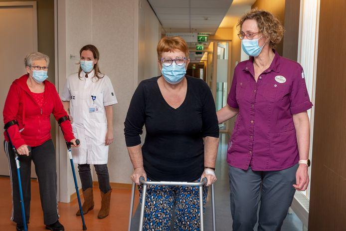 Jeanne Scholten op krukken (begeleid door Bo Cozijnsen - ETZ) en Wies Spapen met looprek  (begeleid door Renate Groothuis - De Wever) revalideren na hun knieoperatie in De Hazelaar.
