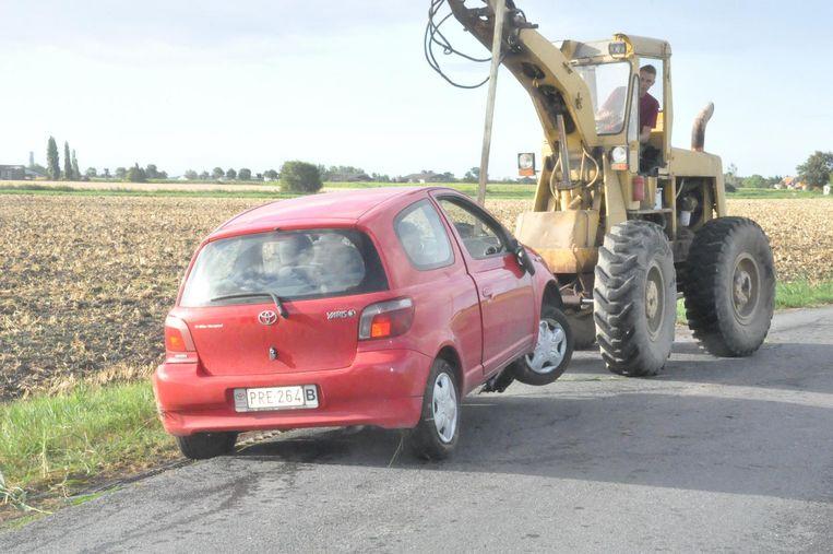De Toyota Yaris wordt uit de gracht getakeld.
