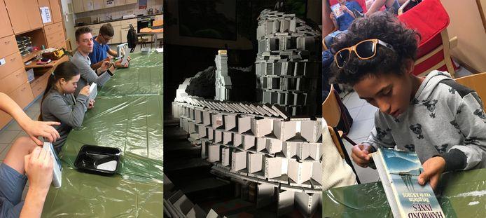Centraal de Boekentoren van Babel met links en rechts de leelringen van Sint-Franciscus aan het werk.