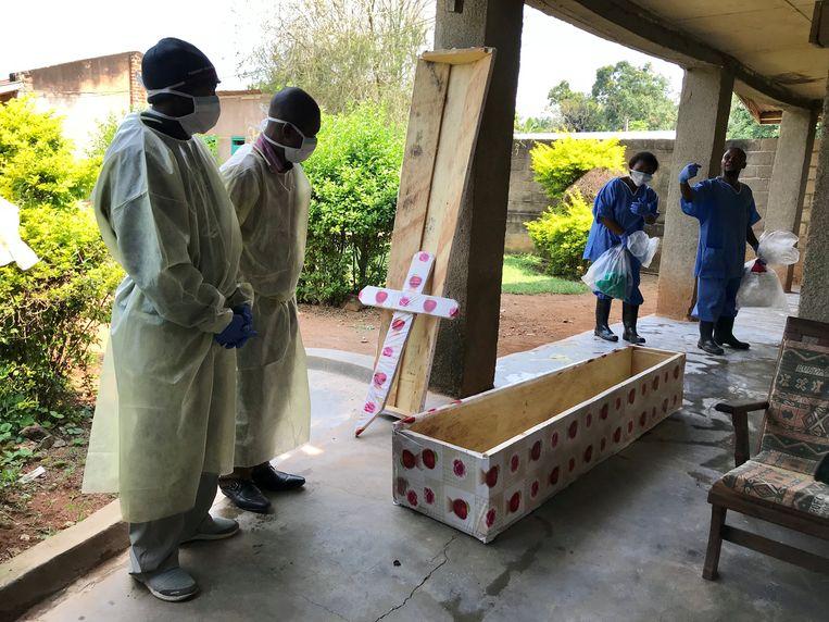 Gezondheidsmedewerkers bereiden zich voor om een van de slachtoffers te begraven.