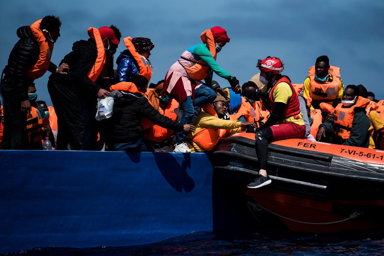 Een lifeguard van de Spaanse ngo Open Arms helpt migranten in volle zee aan boord van hun boot. Beeld Getty Images