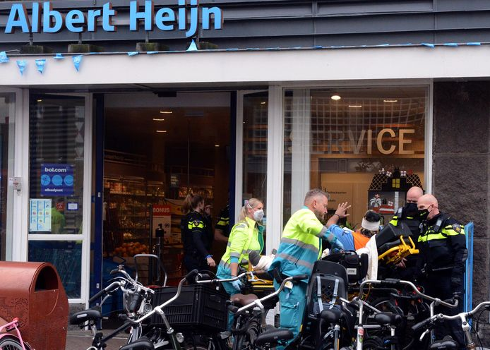 In de Grote Marktstraat ontfermen medewerkers van de ambulance zich over een gewonde medewerker bij de Albert Heijn.