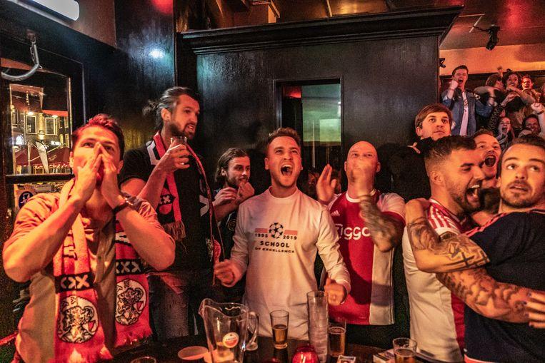 Voetballiefhebbers kijken in een café naar een Champions League-wedstrijd van Ajax. Beeld Joris van Gennip