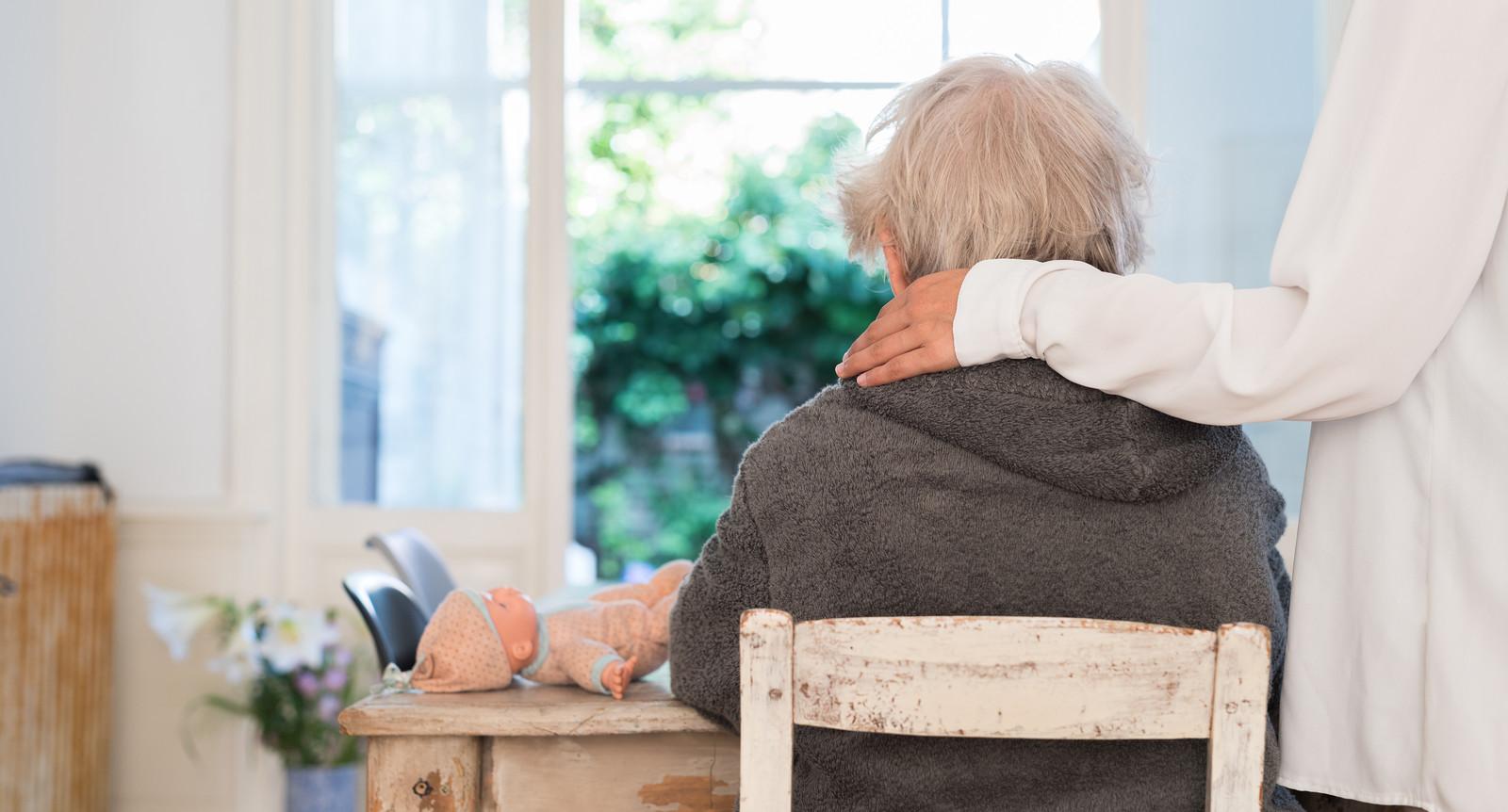 Een familielid legt haar hand op de schouder van een demente oudere.
