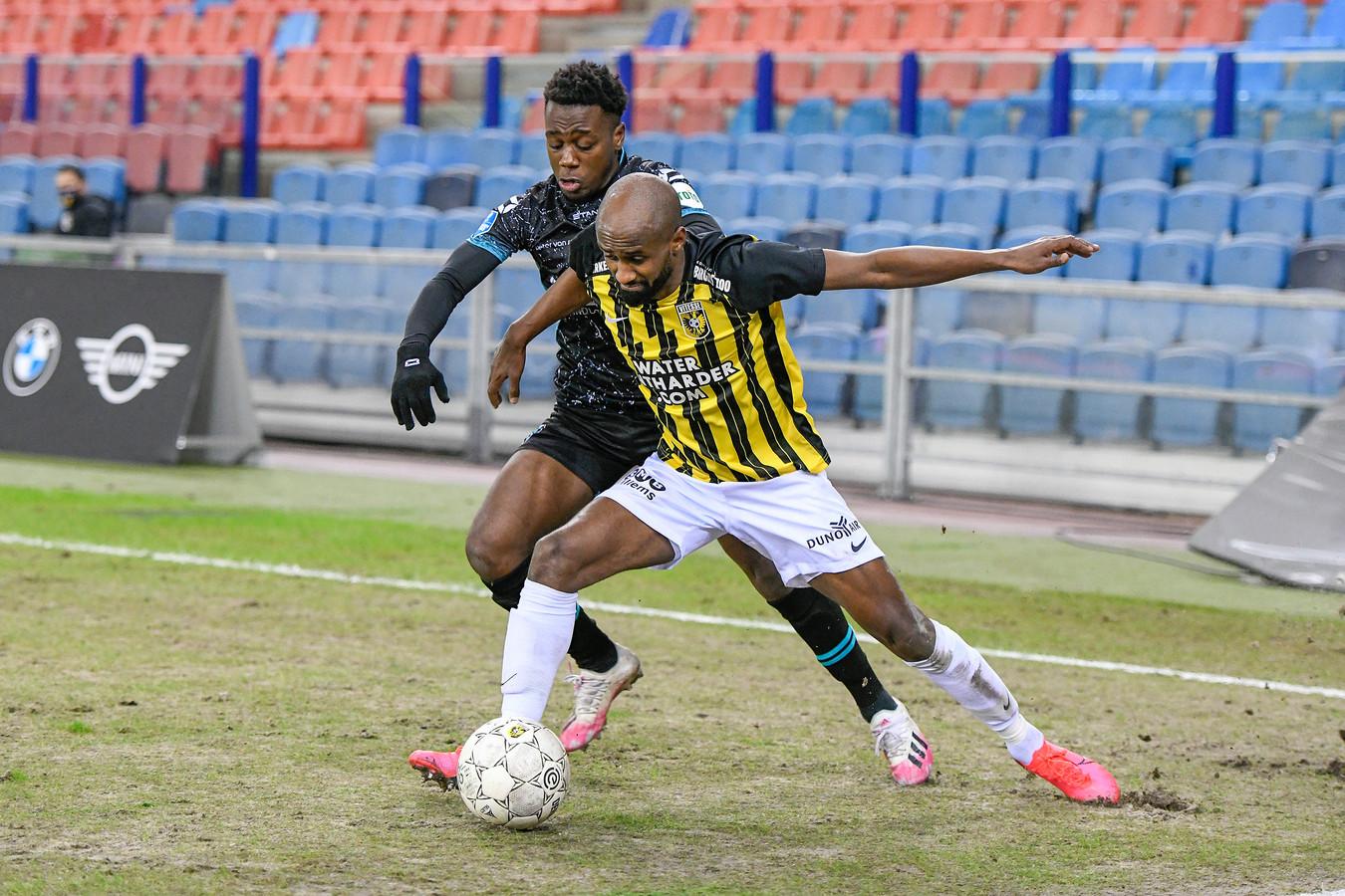 Thierry Lutonda van RKC en Vitessenaar Eli Dasa strijden op een slecht veld in GelreDome om de bal.