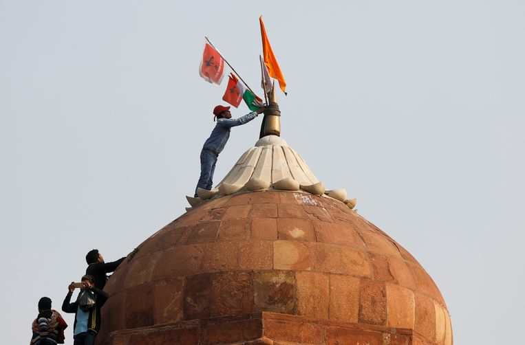 Een man plant een vlag op een koepel van het historische Rode Fort in New Delhi. Beeld Reuters
