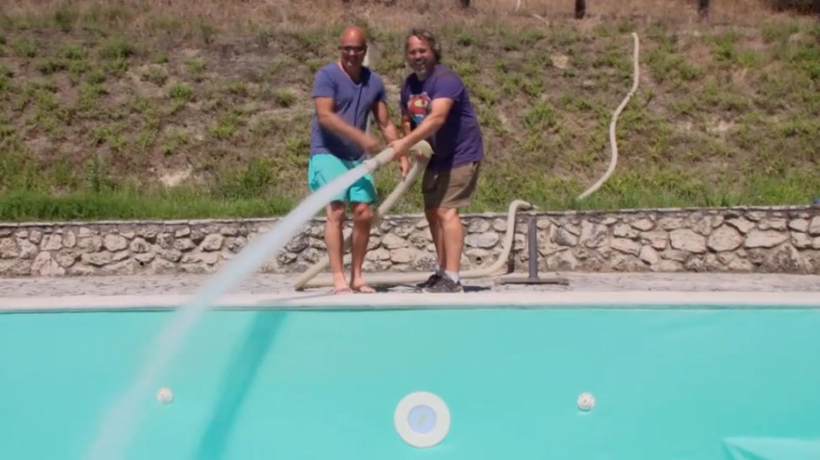 Jean Paul en een vriend vullen het zwembad.