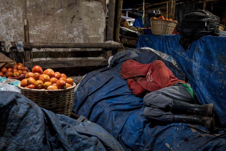 Als gevolg van de lockdown worden handelaren opgeroepen op de markt te blijven slapen, om een verdere virusuitbraak te voorkomen.   Beeld AFP