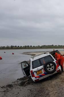 Politieboot strandt op lage Rijn, opgetrommelde politiewagen en shovel ook vast