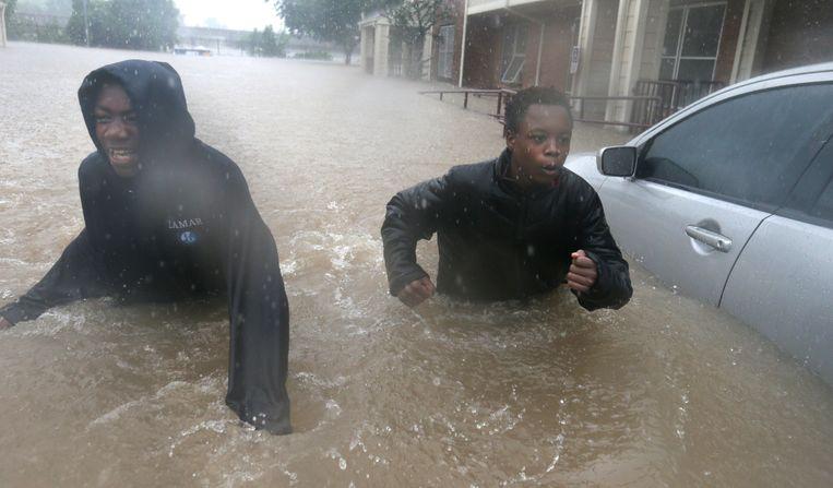Twee jongens brengen zich in veiligheid in een overstroomd Houston. Beeld ap