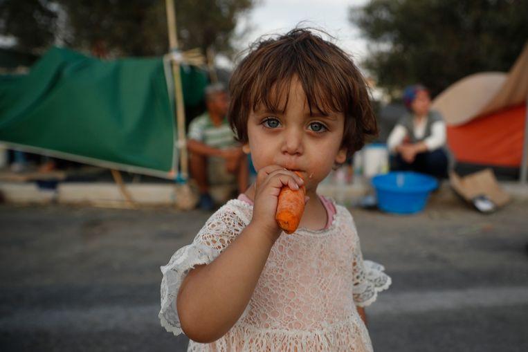 Een meisje eet een wortel nabij het vernielde vluchtelingenkamp Moira op het Griekse eiland Lesbos. (16/09/2020)