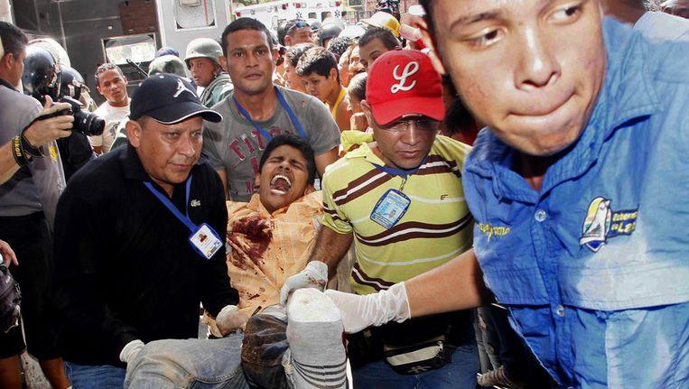 Een gewonde gevangene wordt weggedragen uit de Uribana-gevangenis. Beeld ap