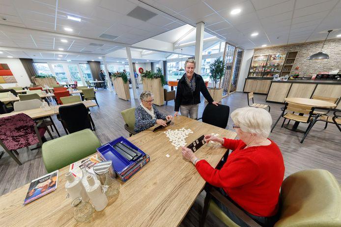 Zevenbergen - 23-1-2018 - Foto: Marcel Otterspeer / Pix4Profs - De Westhoek is gerenoveerd, en sinds korte tijd is ook de entree en de nieuwe centrale zaal klaar. Pitricia Koomans is gastvrouw en is hier in die nieuwe zaal met de rummikubbende dames Jopie Eland en Toos Groeneveld.