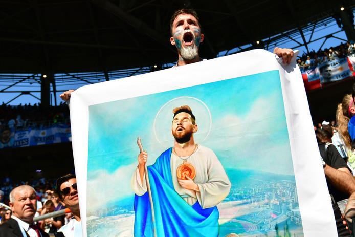 Een supporter van Argentinië houdt een poster omhoog waarop Lionel Messi is afgebeeld als Jezus.