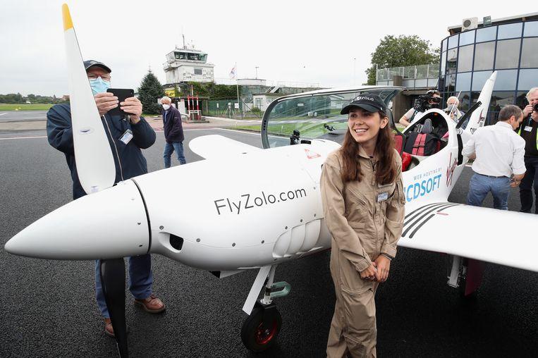 De 19-jarige Belgisch-Britse piloot Zara Rutherford poseert voor fotografen op het vliegveld in het Belgische Wevelgem. Rutherford vertrok gisteren voor een recordpoging om als jongste vrouw ooit solo rond de wereld te vliegen. De tocht in een ultralicht sportvliegtuigje overbrugt meer dan 51.000 kilometer en zal ongeveer drie maanden duren.  Beeld REUTERS