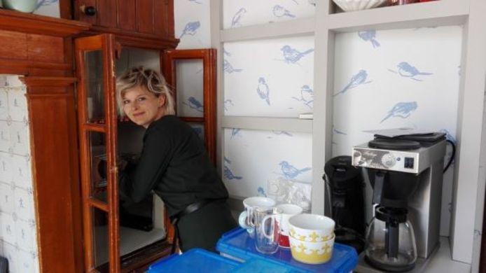 Conservator Stephanie Rompa plaatst het serviesgoed terug in de oude muurkast van Stadsmuseum Woerden.