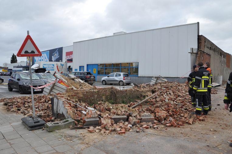 Wind doet muur instorten op geparkeerde wagens aan de Weba in Deinze. Beeld Wouter Spillebeen