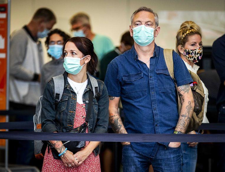 Mensen staan te wachten op de luchthaven van Schiphol. Beeld ANP
