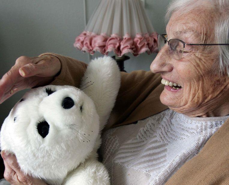 Robotzeehond Paro wordt gebruikt om ouderen met dementie te activeren. Beeld ANP