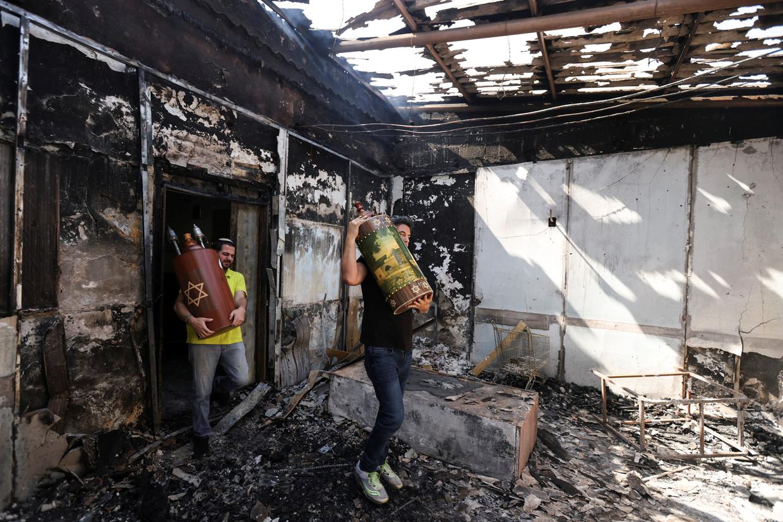 Joden halen thorarollen uit een synagoge in Lod die door Arabieren in brand is gestoken. Beeld REUTERS