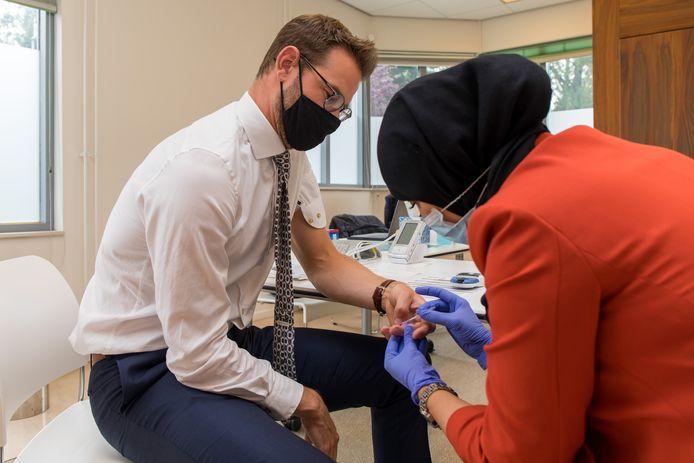 Als eerste wordt de gezondheid van de Rotterdamse wethouder Sven de Langen gecontroleerd door apotheker Bouchra el Bouazzaoui.