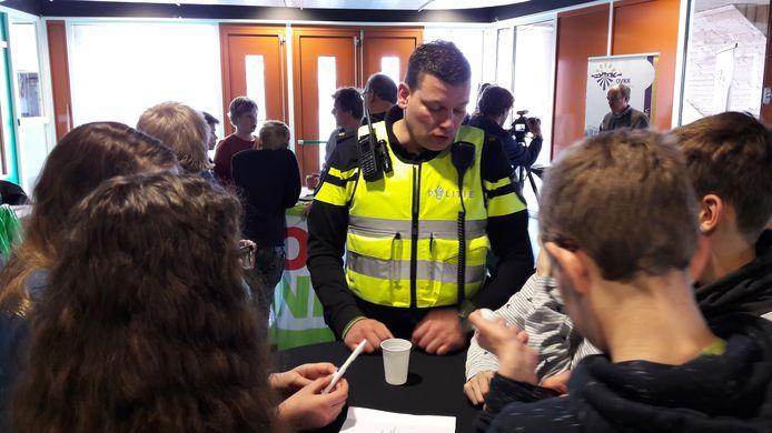 Wijkagent Urban Monninkhof geeft antwoord op vragen van leerlingen van de Capellenborg.