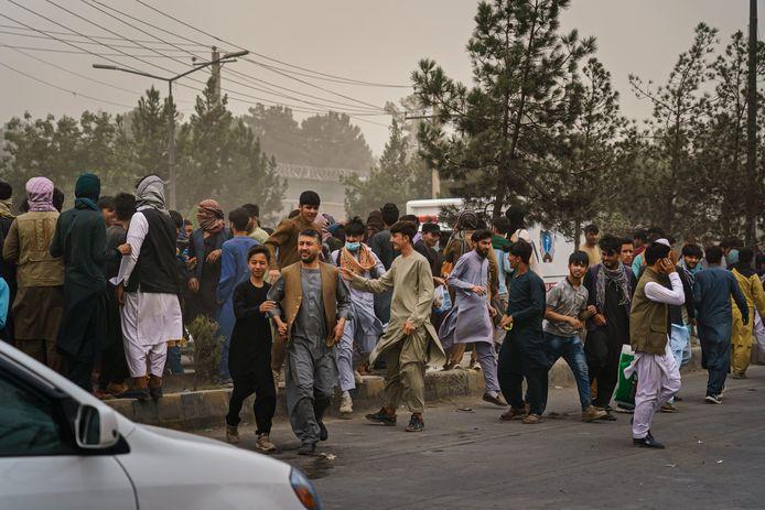 Een menigte wanhopige Afghanen in de buurt van de internationale luchthaven in Kaboel. Verschillende mensen vluchten in paniek weg nadat talibanstrijders de massa uit elkaar probeert te drijven met vuurwapens, zwepen, stokken en scherpe voorwerpen. Daarbij raakten verschillende mensen gewond.