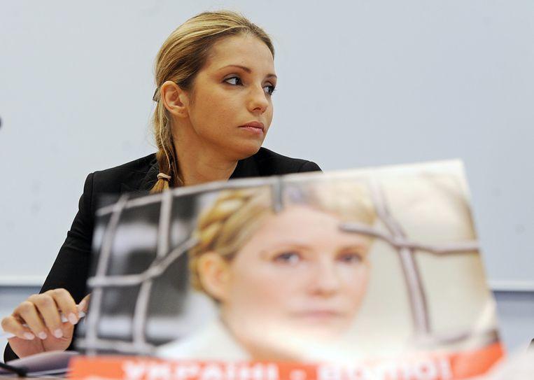Eugenia Timoshenko gisteren bij een persconferentie in Praag met een verkiezingsposter van haar moeder, die sinds oktober gevangen zit in de Oekraïne. Beeld EPA
