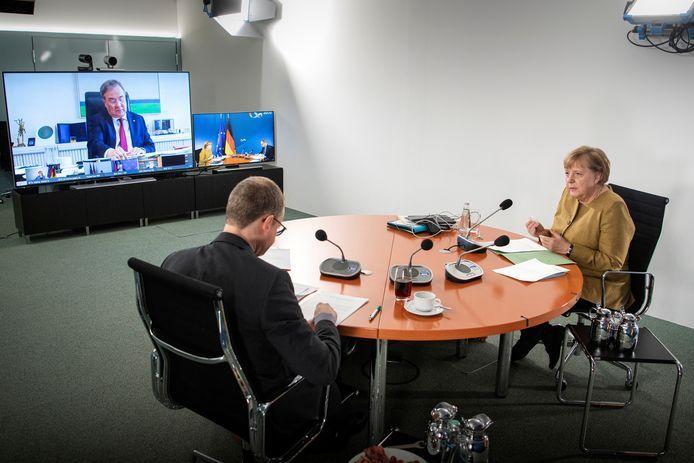 De Duitse bondskanselier Angela Merkel en burgemeester van Berlijn Michael Mueller via een videoverbinding in gesprek met Amin Laschet, premier van de deelstaat Noordrijn-Westfalen.