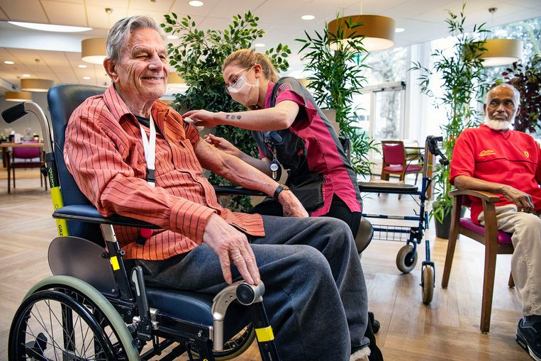 Voormalig psycholoog Bart Uiterlinde (91) ondergaat lachend de prik. De bewoner van verpleeghuis in Haarlem voelt zich daarna 'kiplekker', zegt hij. Jamiel Ramzam kijkt toe. Beeld