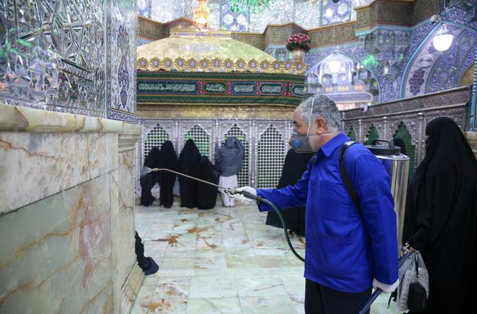 Een man besproeit de Fatima Masumehmoskee in Qom met een desinfectans tegen het coronavirus.