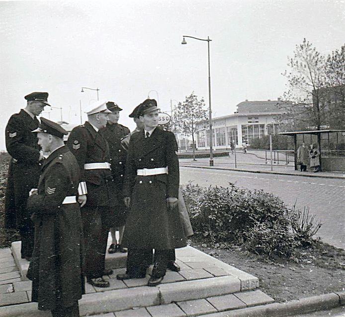 Politiefunctionarissen wachten op de dingen die komen gaan. Met eromheen plukjes Rotterdam anno 1957.