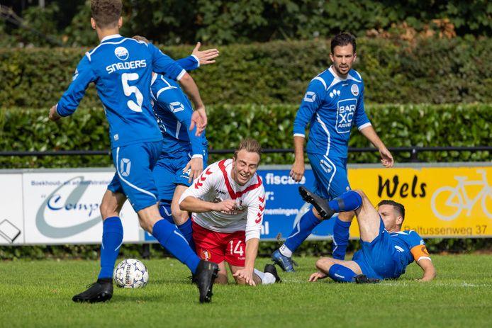 Twan Beijer van RKSV Driel krijgt geen poot aan de grond, de tackle is van Ralf van Bussel van Eldenia.