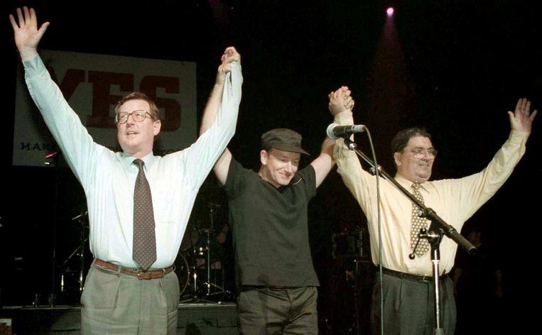 Op Goede Vrijdag 1998 brengt rockzanger Bono van U2 de handen samen van protestant David Trimble en katholiek John Hume. Beeld BELGAIMAGE