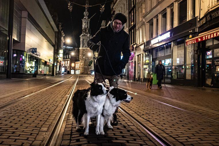 Mensen laten hun honden uit in de verder lege straten van Amsterdam tijdens eerste nacht van de avondklok. Beeld Joris van Gennip