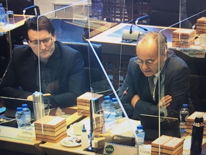 Beschermd door kuchschermen voert Frank Kuijpers (CDA) het woord over de Zanddijk. Naast hem zijn partijgenoot Jeffrey Oudeman