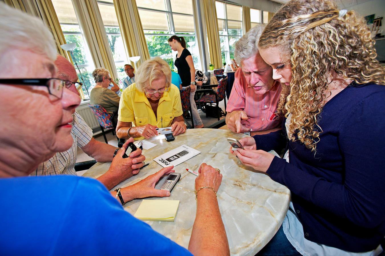 Uit het archief: deelnemers aan de Zomerschool krijgen uitleg in het gebruik van een mobieltje.