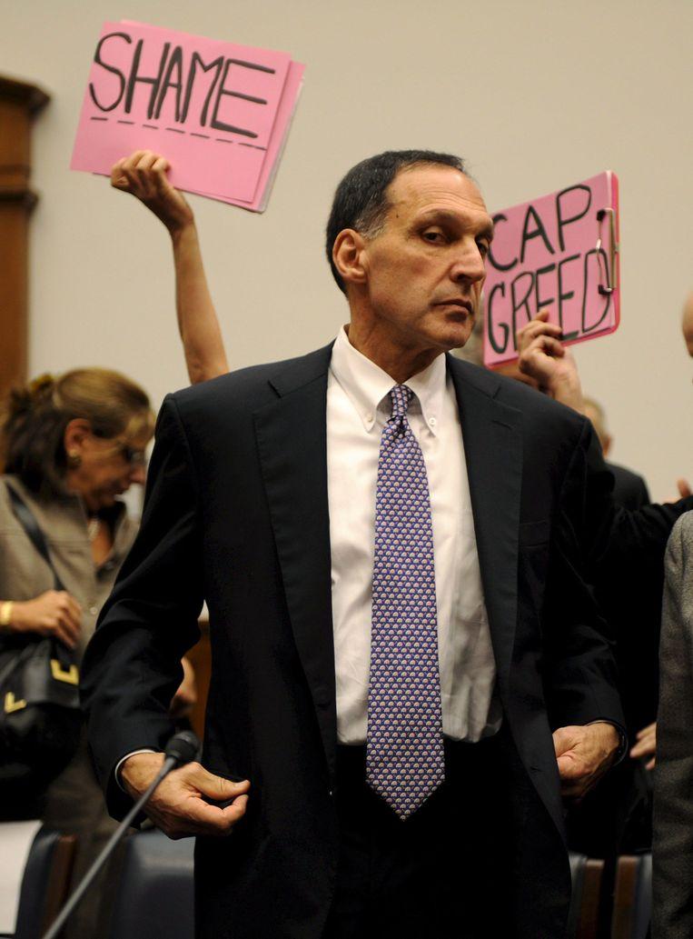 Richard Fuld, topman van het failliete Lehman Brothers, wordt tijdens een hoorzitting in het Congres omstuwd door betogers (2008). Beeld BELGAIMAGE