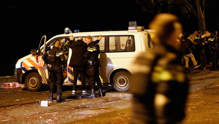 Agenten van de politie in Rotterdam verrichten tijdens de jaarwisseling een arrestatie vanwege wapenbezit. Beeld anp