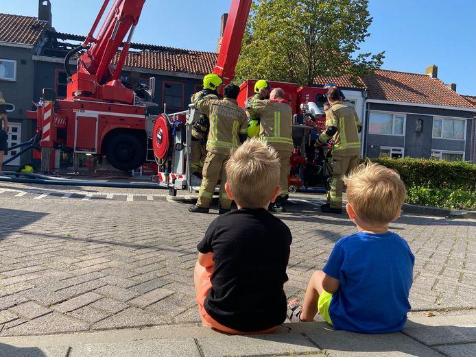 Caleb en Ethan kijken naar de brandweermannen die net de brand bij de bakker hebben geblust.